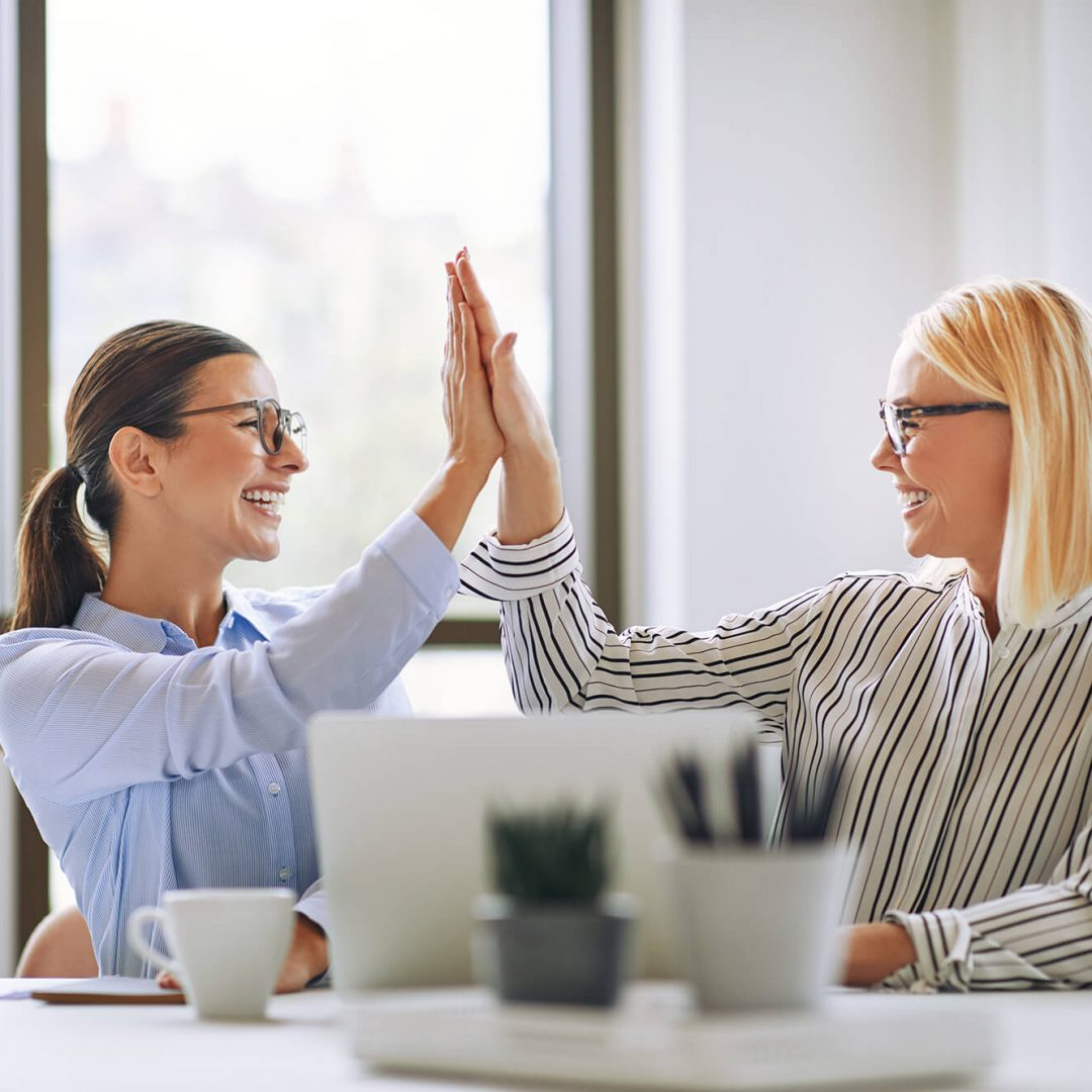 two-smiling-businesswomen-high-fiving-together-in-DDNACN5-1.jpg